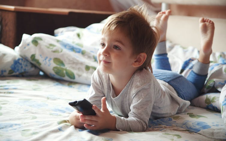 Little boy on bed watching TV