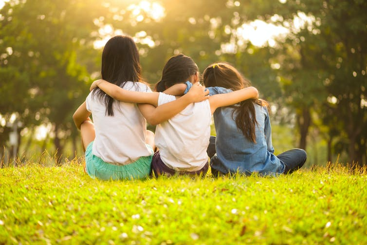 Three girls sitting in a park with their arms around each other.