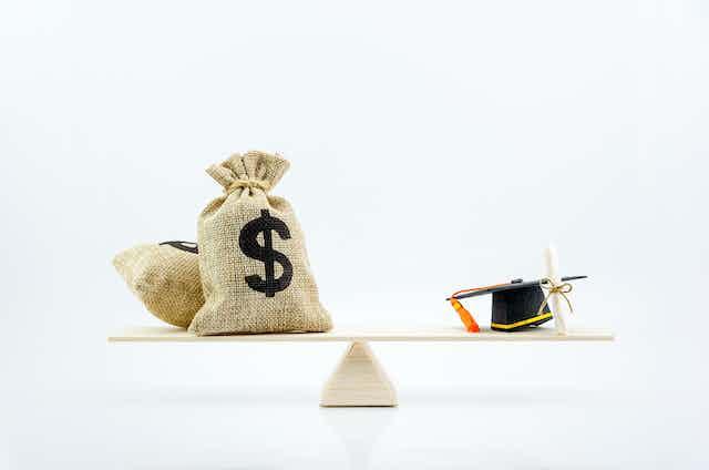 bags of money balanced against academic degree