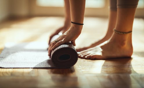 Pies y manos de una persona que se dispone a hacer ejercicio en el interior de una vivienda sobre una esterilla.