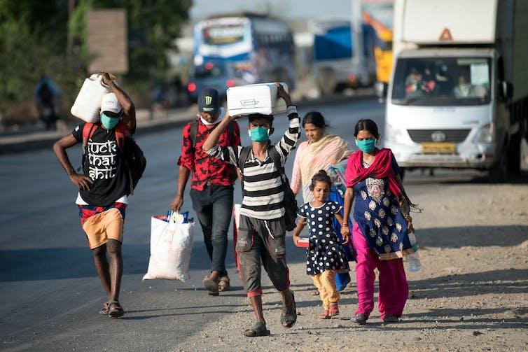 Trabajadores migrantes caminan por la carretera en su viaje de vuelta a casa durante un confinamiento nacional para luchar contra la propagación de la covid-19.