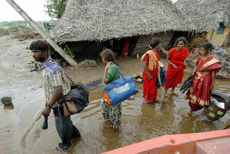 La gente abandona la devastada aldea de Karmavadi con sus pertenencias en el distrito de Nagapattinam, a unos 350 km al sur de Madrás, el 27 de diciembre de 2004, después de que los maremotos azotaran la región