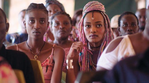 Pople sit in rows in what looks to be a church, looking ahead. The frame is dominated by two striking young women, one with pink braids.
