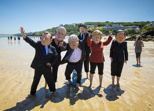 Protesters dress as G7 leaders on a Cornish beach.