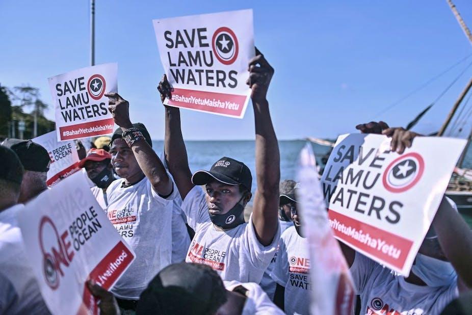 Kenyan fishermen carry placards off the Lamu coast