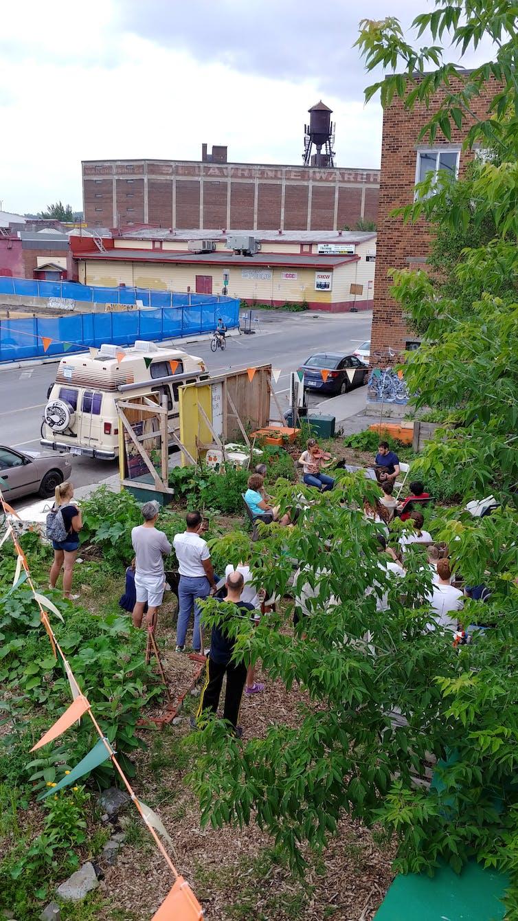 Des gens sont regroupés autour d'un jardin, dans une zone industrielle de la ville