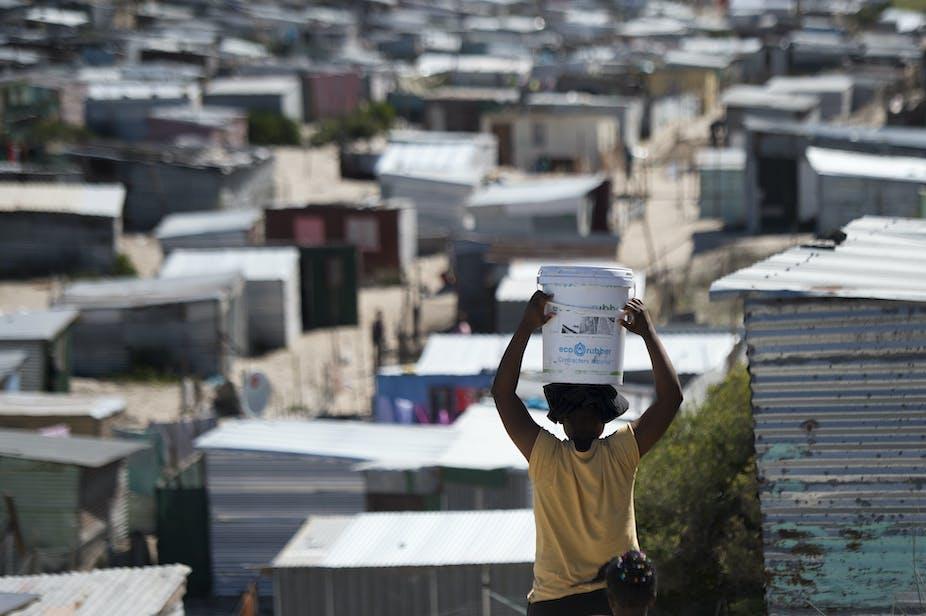 A woman carries a bucket of fresh water to an informal settlement