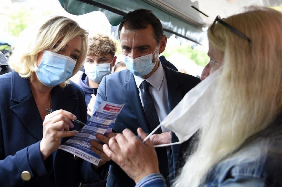 Marine Le Pen signe un tract le 8 juin 2021, lors d'une visite dans un marché de Lunéville aux côtés de la tête de liste RN dans le Grand Est,  Laurent Jacobelli.
