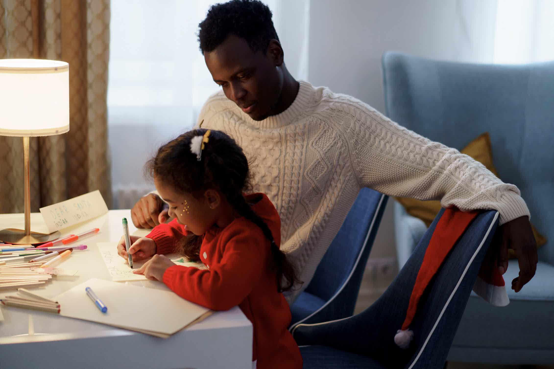 A father sits wtih daughter who is writing at a desk.