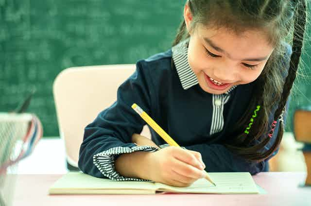 A girl holds a pencil at a desk.