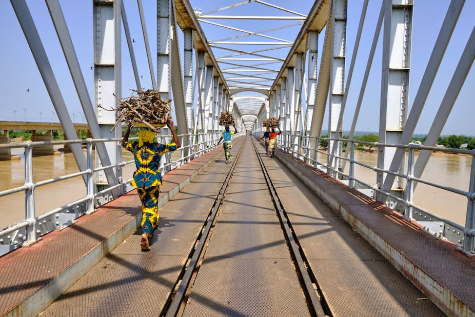 Women with a load on their head crossing river Niger using the railway bridge at Jebba