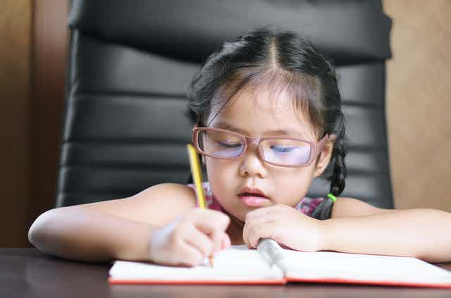 Young girl wearing glasses writes in a notebook.