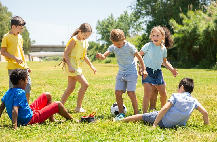 Group of children playing football outdoors in the summer.