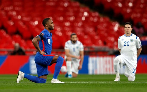 Raheem Stirling takes a knee on the football pitch next to two other football kneeling players