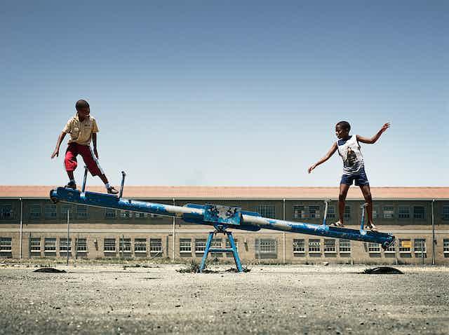 Two boy balancing on seesaw.