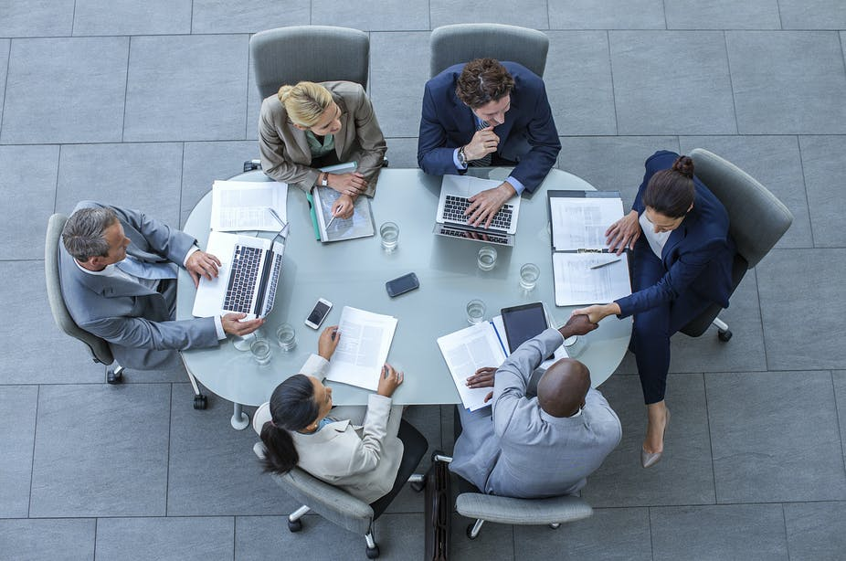 High angle view of people in business attire shaking hands at a conference table in an office.