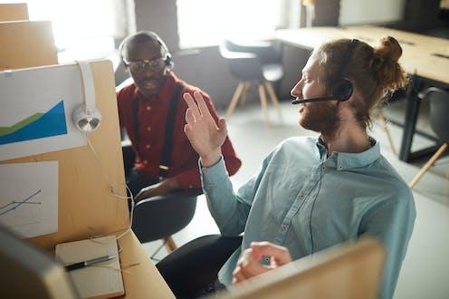 Deux employés côte à côte discutent au travail
