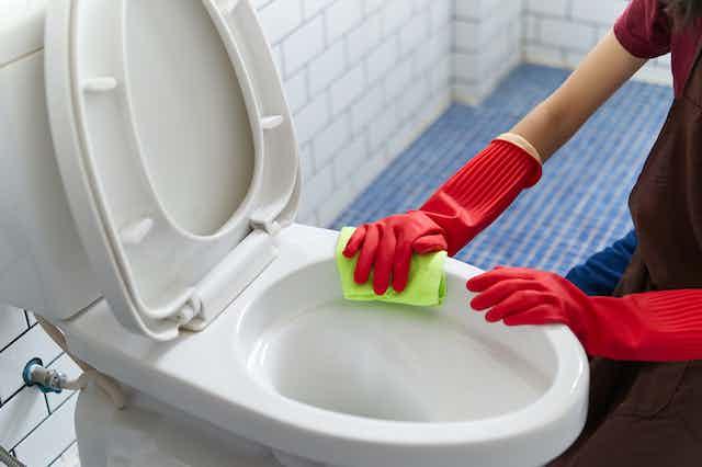 Mujer con guantes de fregar rojos y bayeta limpia inodoro.