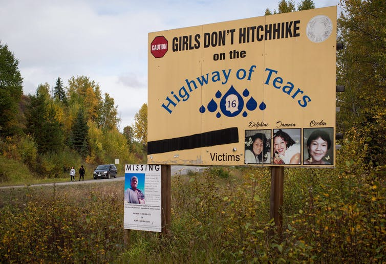 A road sign depicting three missing Indigenous women, reading 'Girls don't hitchhike on the Highway of Tears'