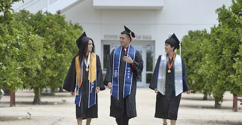 Three college grads speak to one another in their caps and gowns.