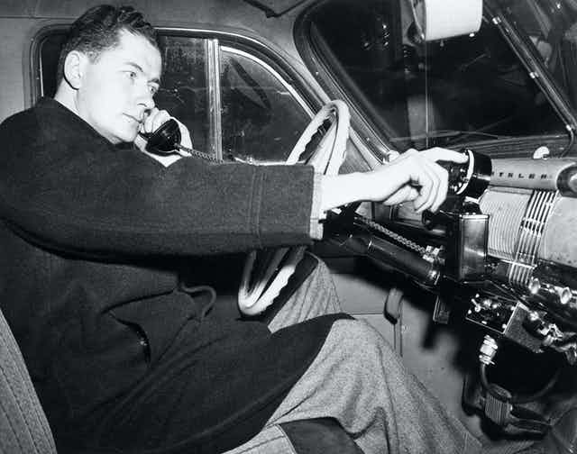 A historic photograph of a man sitting behind the wheel of a 1940s automobile holding telephone handset and dialing a telephone rotary dial installed in the car