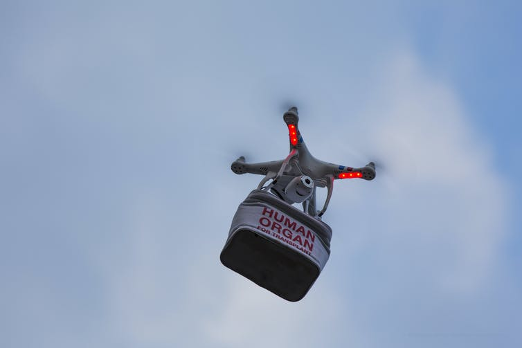 a drone flies carrying a package labelled HUMAN ORGAN