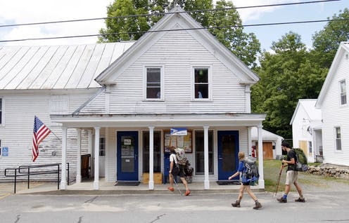 Hikers walk past a white building housing a U.S. post office near the Appalachian trail in maine