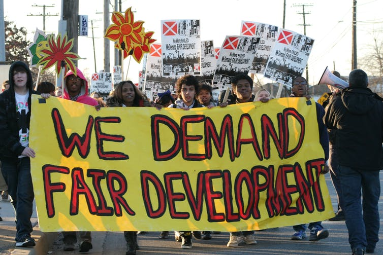Protesters march behind a sign reading 'We demand fair development'.