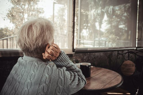 An elderly lady staring out the window