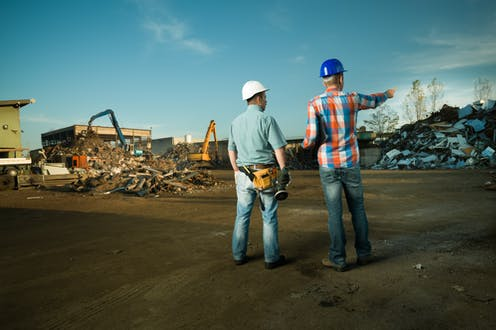 Two men in hard hats look out over a construction waste recycling centre