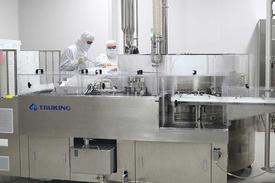 Two people in full protective gear work in a sterile laboratory type of room