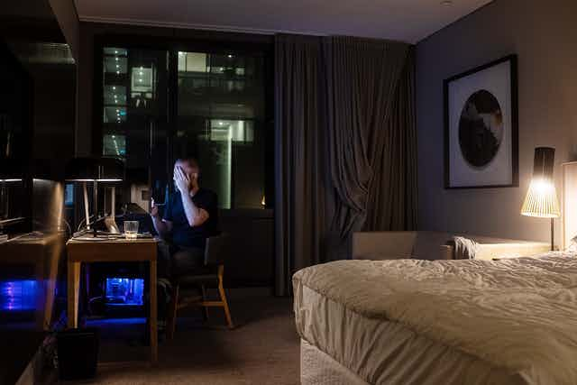 Man covers his face in hotel room at night.