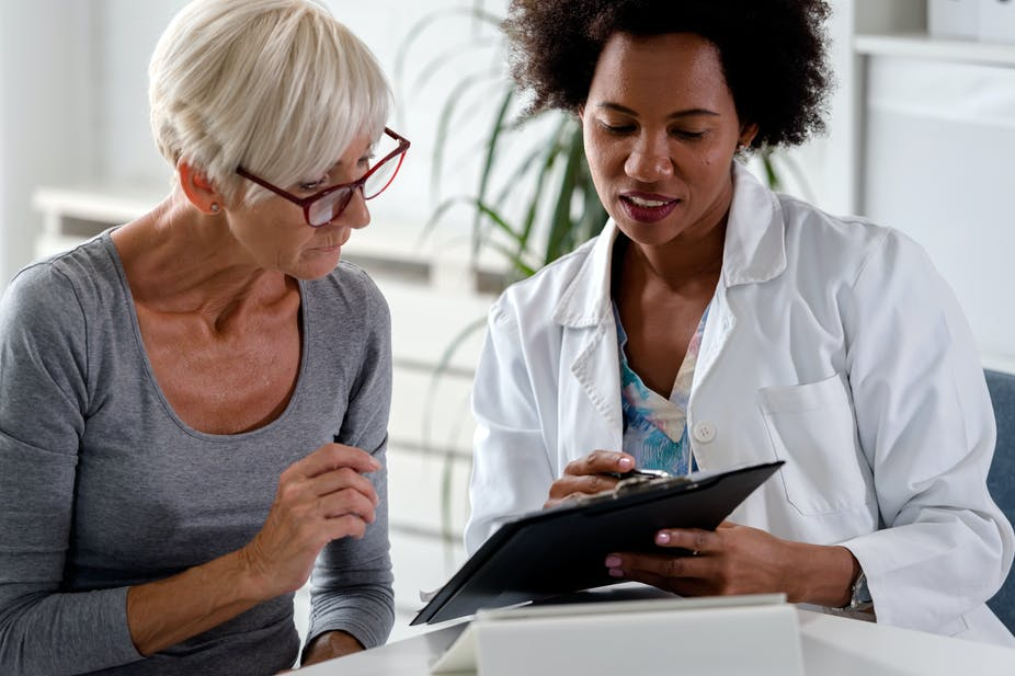 Female doctor using a clipboard to explain something to an older female patient.