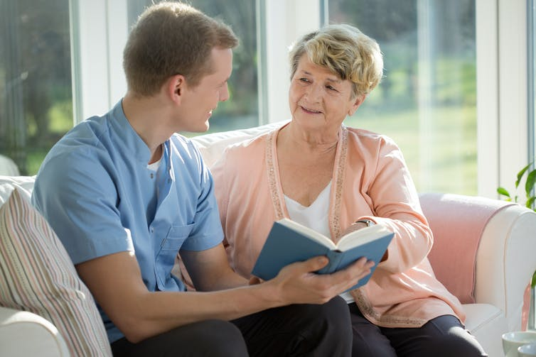 A young man reads a book with an elderly woman.