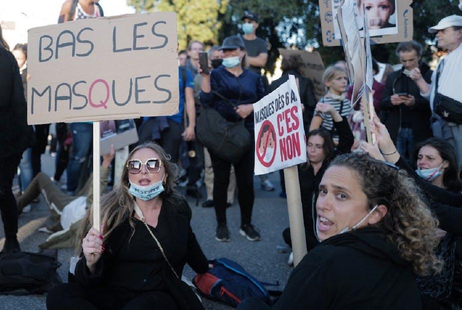 Plusieurs femmes tiennent des panneaux protestant contre le port obligatoire du masque.