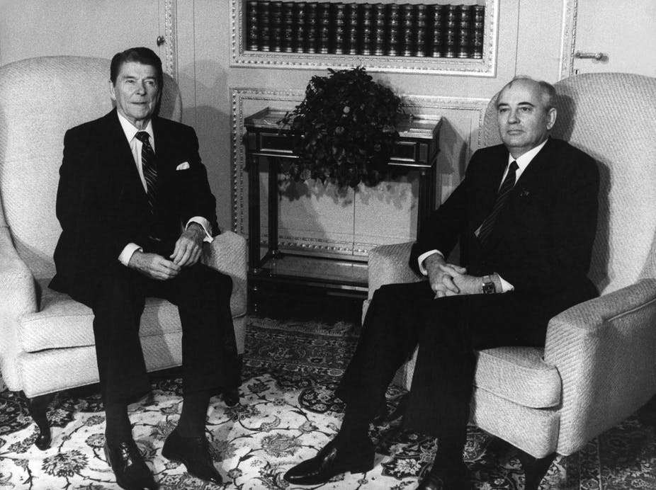 A black and white photo of Ronald Reagan and Mikhail Gorbachev seated in armchairs.