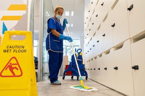 Woman in blue cleaning uniform and face mask sweeps the floor in front of caution wet floor sign