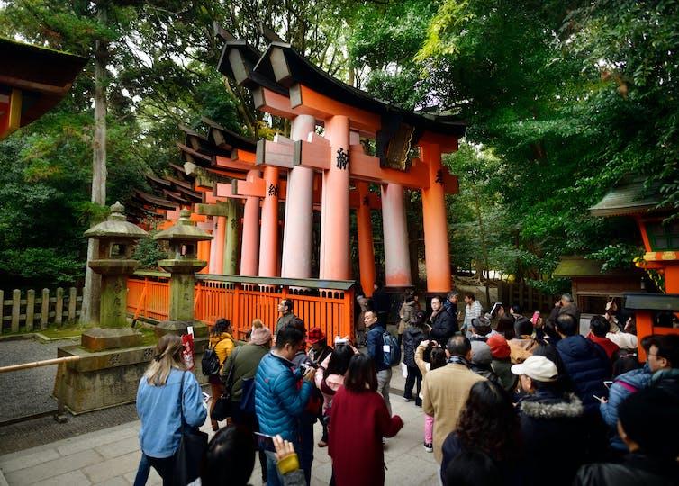 Tourists take the Senbon Torii path in the Fushimi Inari Taisha shrine in Kyoto, Japan
