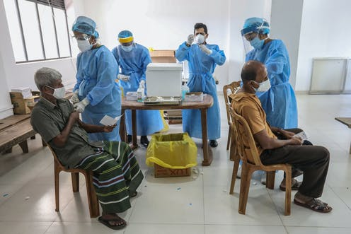 People receive the second dose of China's Sinopharm COVID-19 vaccine at a temporary vaccination center in Colombo, Sri Lanka, 16 June 2021