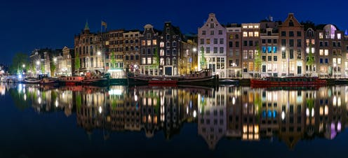 Buildings lit up against a night sky are reflected in the still waters of an Amsterdam canal