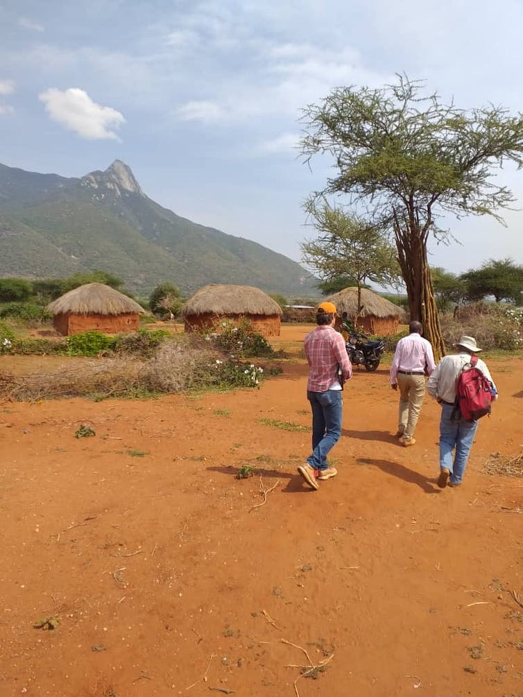 People walk across a reddish dirt area with grass-roofed huts in the background.