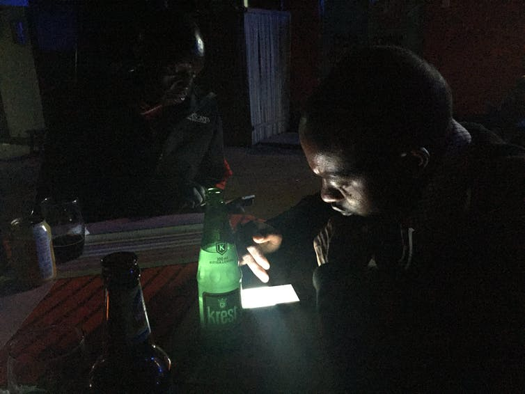 In a darkened room, phone screens light two men's faces.