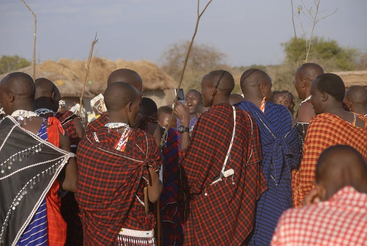 In a crowd of people in traditional Maasai dress, one man holds a mobile phone.