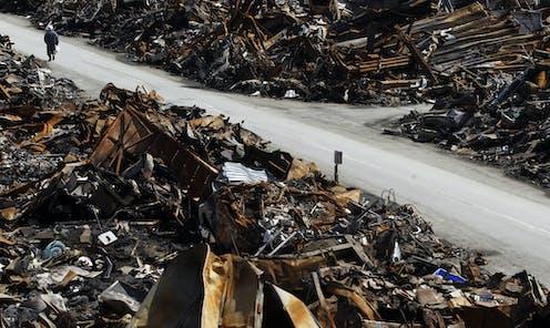 An elderly man walks through burnt debris.