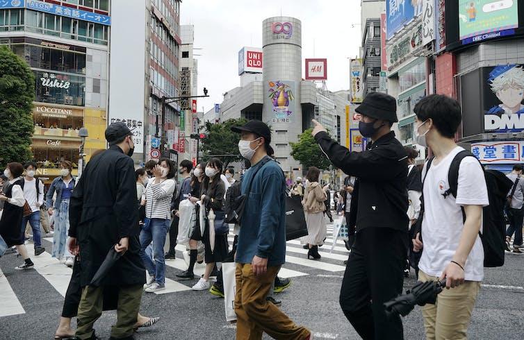 People wearing protective masks walk cross a crossway in Tokyo, Japan.