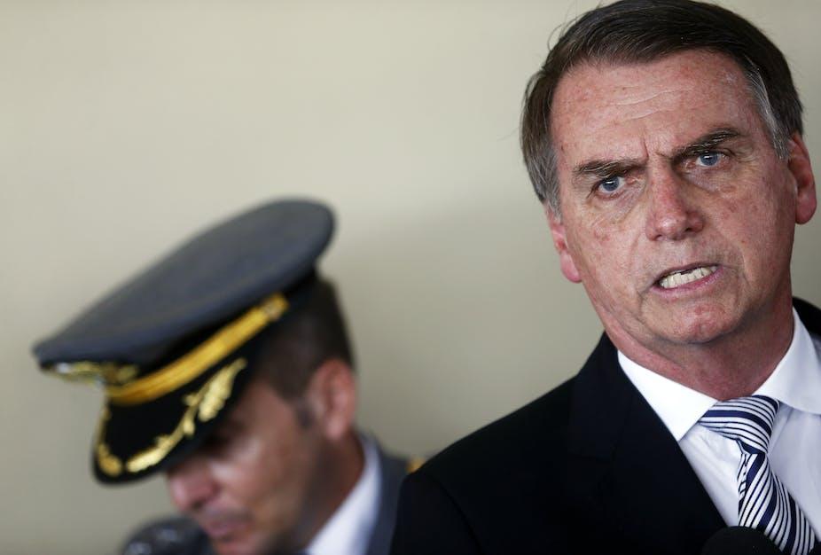 Jair Bolsonaro with a military escort behind him.