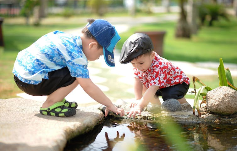 Two children play by water
