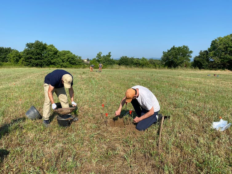 people sifting dirt in field