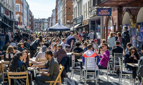 People eating and drinking outside in Soho, London