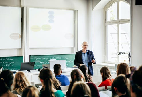 A white male professor teaches a class of students.